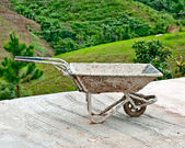 The Old wheelbarrow on mountain background — Stock Photo