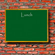 Green menu blackboard with empty space on brick wall background — Stock Photo #11692089