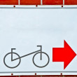 Stock Photo: Guide post park bicycle with red arrow on brick wall background