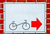 The Guide post park bicycle with red arrow on brick wall background — Stock Photo