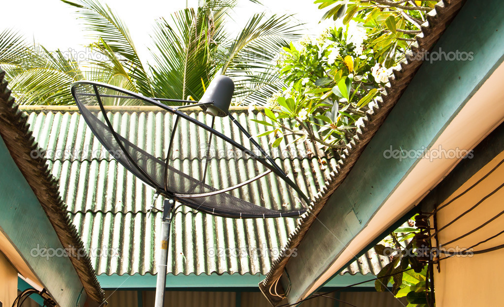 Satellite dish installed on the corner of the house.  Stock Photo #10908645