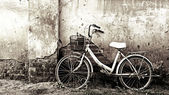 Old bicycle and cracked wall — Stock Photo