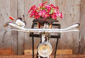 Artificial flowers on bicycle in rainy day — Stock Photo