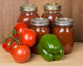 Tomato sauce in jars with tomatoes and peppers — Stock Photo