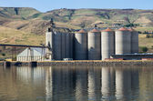 Grain elevator storage on river — Stock Photo