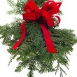 Christmas decoration of live greens and red bow — Stock Photo