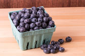 Blueberries in container and on table — Stock Photo