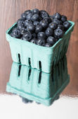 Green container of blueberries on shiny table — Stock Photo