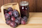 Prune plums with jar of jam — Stock Photo