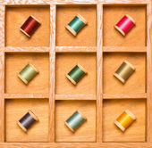 Bright thread on spools in shadow box — Stock Photo