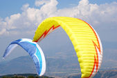 Yellow and blue sailing in the background of blue sky — Stock Photo