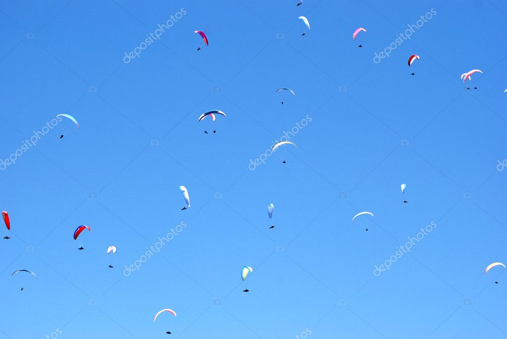 A lot of paragliders of the background of blue sky — Stock Photo #11943078