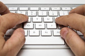 White computer keyboard with hands — Stock Photo