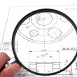 Reviewing technical drawing with magnifying glass. Focus on technical drawing. — Stock Photo