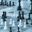 Chess pieces in diferent size on a chess boards - Blue tint — Stock Photo