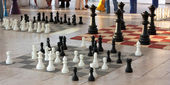 Chess pieces in diferent size on a chess boards — Stock Photo