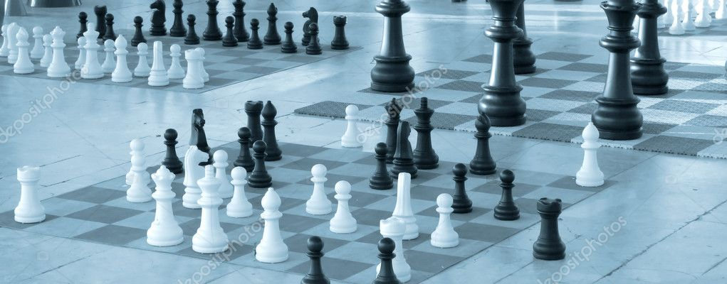 Chess pieces in diferent size on a chess boards - Blue tint  Stock Photo #11922513