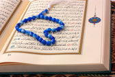The Holy Koran page with blue rosary — Stock Photo