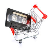 Compact casette in miniature shopping cart isolated on white — Foto de Stock