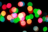 Defocused christmas lights with black background — Stock Photo