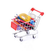 Color pencils and some stationery in miniature shopping cart iso — Stock Photo