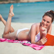 Woman is reading a book on a beach — Stock Photo #10945818