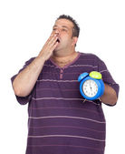 Fat man with a blue alarm clock yawning — Stockfoto