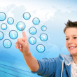 Boy pointing at web icons with futuristic interface. — Stock Photo