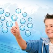 Boy pointing at web icons with futuristic interface. - Stock Photo