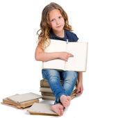 Oturan kız, eski kitaplar kazık. — Stok fotoğraf