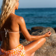 Young woman doing yoga at seaside. — Stock Photo
