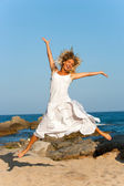 Attractive woman in white jumping outdoors. — Stock Photo
