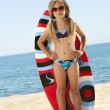 Cute girl standing with surfboard on beach. — Stock Photo