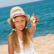 Sweet girl on beach showing shell. — Stock Photo