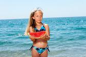 Cute girl eating watermelon on beach. — Stock Photo