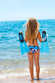 Cute girl facing the sea with goggles and flippers. — Stock Photo