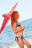 Sweet girl walking with umbrella on beach. — Stock Photo