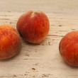 Stock Photo: Three ripe peaches on wooden surface
