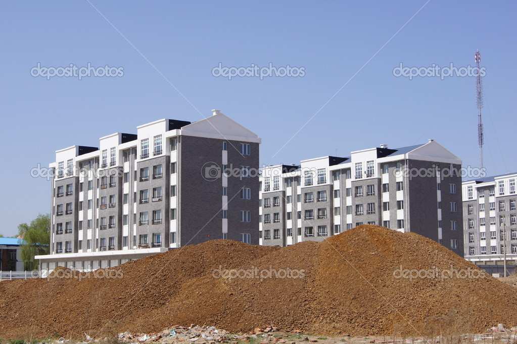 The new model gray apartment houses in the Chinese city of Heihe on the background of blue sky and a heap of soil in the foreground.  2012.  Stock Photo #10859689
