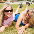 Two woman friends lying on the grass — Stock Photo