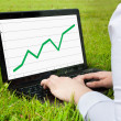 Woman working outdoors on laptop showing upward line graph — Stock Photo