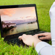 Woman searching holiday destination outdoors on laptop — Stock Photo
