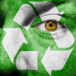 Recycling symbol painted on mans face - Stock Photo