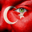 Flag painted on face with green eye to show Turkey support — Stock Photo