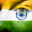 Flag painted on face with green eye to show india support — Stock Photo