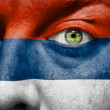 Flag painted on face with green eye to show Serbia support — Stock Photo