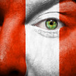 Flag painted on face with green eye to show Peru support — Stock Photo