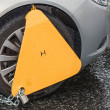 Yellow triangle wheel clamp on an illegally parked car — Stock Photo