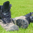 Two firm black leather boots covered in mud — Stock Photo