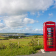 Red phone booth landscape — Stock Photo